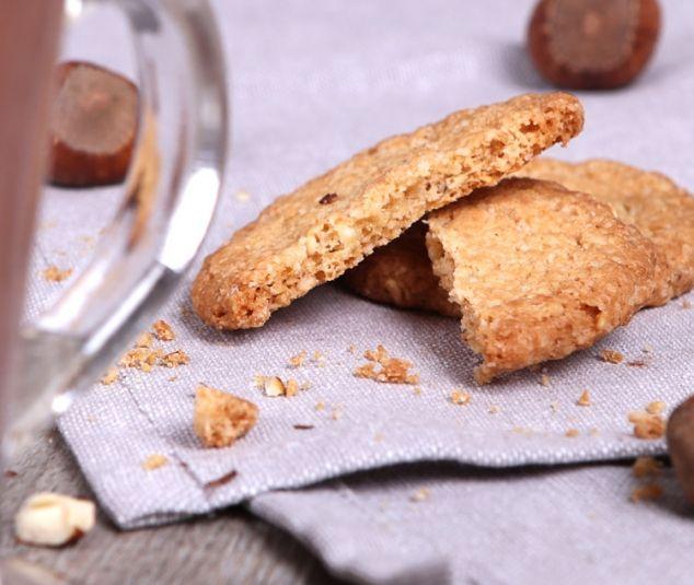 Ciasteczko owsiane z blankietem na pięknej lnianej ściereczce obok szklanki z gorącą czekoladą.